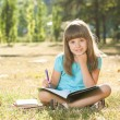 Little schoolgirl doing her homework in the park — Photo #60724993