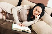 Woman lying on the sofa and reading a book — Stock Photo