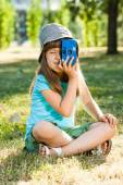 Girl sitting in park and holding photo camera — Stock Photo