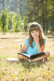 Little schoolgirl doing her homework in the park — Stock Photo
