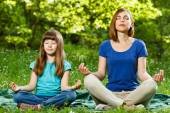 Mother and daughter meditating — Stock Photo