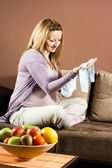 Pregnant woman holding baby clothes — Stock Photo