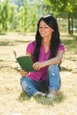Woman sitting in the park and enjoys reading a book — Stock Photo