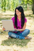 Woman sitting in the park and using her laptop — Stock Photo
