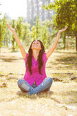 Woman is sitting in the park with her arms outstretched — Stock Photo