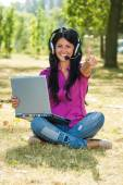 Woman using laptop and headset — Stock Photo
