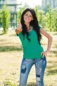 Woman standing in the park and showing thumb up — Stock Photo