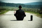 Businessman sitting on country road and meditating — Stock Photo