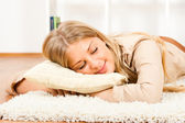 Woman napping on carpet — Stock Photo