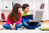 Cute little girl and little boy are using laptop — Stock Photo