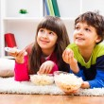 Little girl and little boy enjoy eating popcorn — Stock Photo #66820919