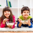 Cute little girl and little boy are eating cereals — Stock Photo #66821179