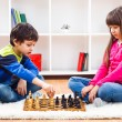 Little boy and little girl are playing chess — Stock Photo #66821237