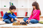 Little boy and little girl are playing chess — Stock Photo