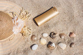 Suntan lotion bottle with straw hat, shells and rocks in the sand — Stock Photo