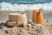 Suntan lotion bottles and hat on the beach — Stock Photo