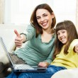 Mother and daughter sitting and using laptop — Stock Photo #69537215