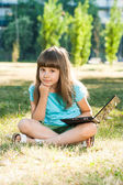 Beautiful little girl sitting in park with her laptop — Stock Photo