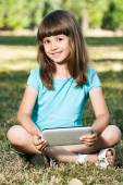 Little girl sitting in park with her tablet computer — Stock Photo