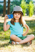 Girl sitting in park and holding photo camera — Foto Stock