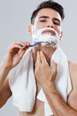 Handsome man shaving — Stock Photo