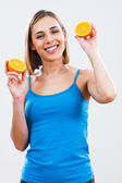 Woman is holding slices of orange — Stock Photo