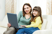 Mother and daughter sitting and using laptop — Stock Photo
