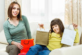 Mother and daughter sitting on sofa after shopping — Stock Photo