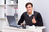 Businessman sitting in his office and showing thumb up — Stock Photo