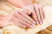 Beautiful woman's hands on towel — Stock Photo