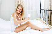 Woman is sitting on bed in her bedroom and putting lotion on her body — Stock Photo