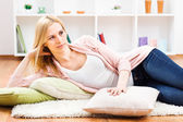 Blonde woman lying on carpet in her living room — Stock Photo