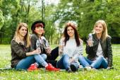 Girls are sitting in the park and holding a bottle of water — Stock fotografie