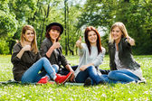 Girls sitting in the park and showing thumbs up — Stock Photo