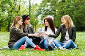 Girls are sitting in the park and drinking water — Stock Photo