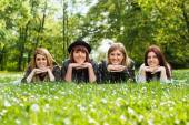 Four young girls lying down in the park — Stockfoto
