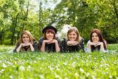 Vier jonge meisjes liggen in het park — Stockfoto
