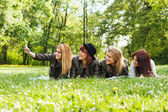 Four cheerful friends lying down in the park — Stock Photo