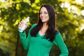 Kobieta stoi w parku z wody — Zdjęcie stockowe