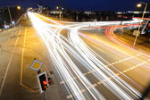 Car light trails on the brisk intersection — Stock Photo
