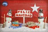 Two snowmen holding a sign with the words Merry Christmas written on spanish — Foto de Stock