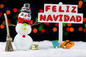 Snowman with a Merry Christmas signpost written on spanish — Stock Photo