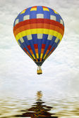 Colorful hot air balloon reflecting in water — Stock Photo
