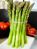 Asparagus bundled to a pack. tomatoes in the background — Stock Photo