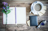 Cup of coffee on rustic wooden table with open books — Stock Photo