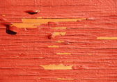 Worn yellow wood with red exfoliated paint — Stock Photo