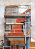 Old house under repair with scaffold and tarpaulin — Foto de Stock