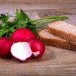 Fresh red radish parsley and bread on old wooden surface — Stock Photo #53086777
