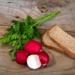 Fresh red radish parsley and bread on old wooden surface — Stock Photo #53086813