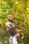 Smiling girl holding a red dog in autumn Park — Foto Stock